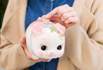 画像_ブタの貯金箱にお金を入れる人